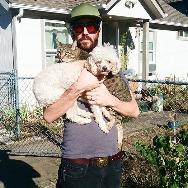 Rex with a beard and sunglasses holding a small dog and a cat at the same time. The dog doesn't look thrilled but that's just the dog's permanent expression I think.